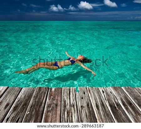 Woman in bikini lying on water at tropical beach - stock photo