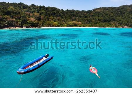 woman in bikini relaxing on turquoise beach, top view - stock photo