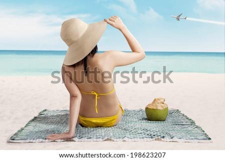 Woman in bikini sitting on the beach enjoying summertime - stock photo