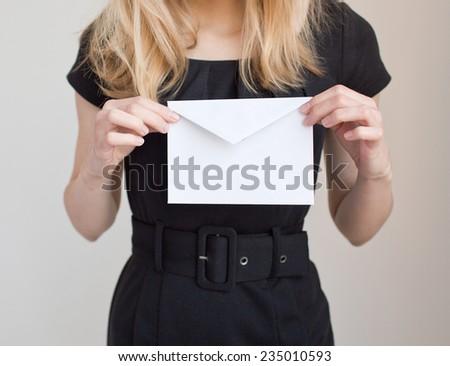 Woman in black dress holding  white envelope - stock photo