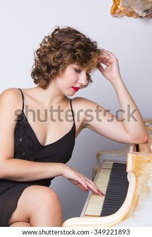 Woman in black dress sitting near grand piano. - stock photo