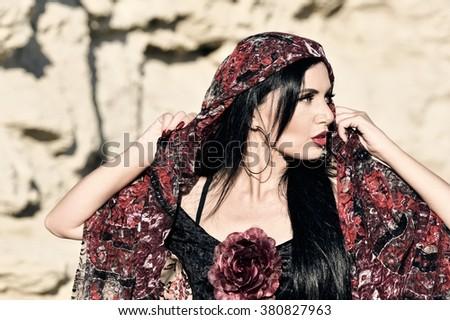 Woman in black dress stay in dancing pose.Portrait of Flamenco dancer in yellow rock background. Photo of flamenco dancer. Beautiful brunette woman, flamenco dancer in natural background - stock photo