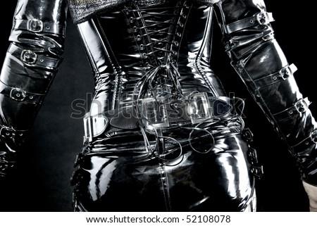 woman in black latex uniform, corset, back - stock photo