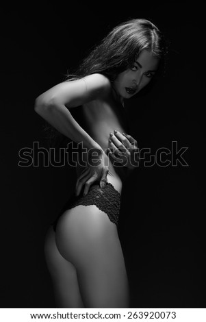 woman in black panties cover her breast, monochrome - stock photo