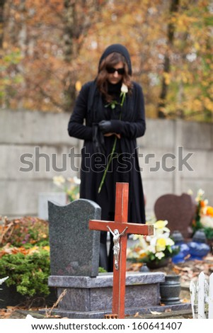 Woman in black standing above headstone holding white rose - stock photo