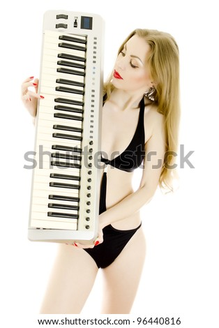 Woman in black swimsuit posing with Piano keyboard. Isolated on white. - stock photo
