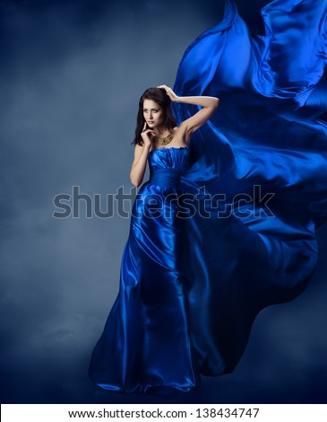Woman in blue dress with flying silk fabric, Model posing and cloth fluttering on wind - stock photo