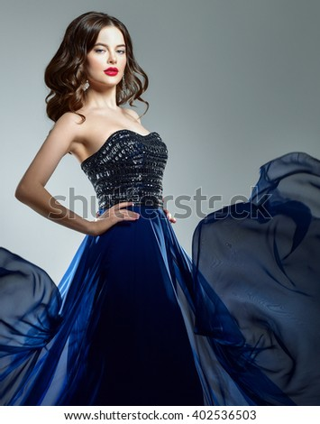 Woman in blue evening dress flying on wind. Young beauty woman in waving dress. Dancer in silk dress. - stock photo