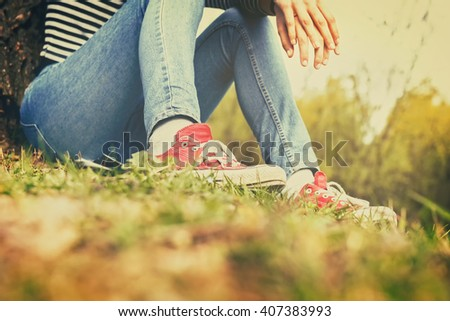 Woman in blue jeans and red canvas sneakers sitting in a grass on a hot summer day. Retro styled photo. - stock photo