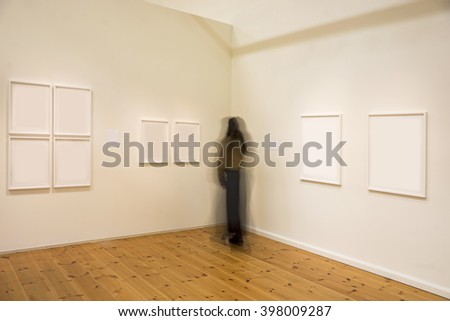 Woman in blurred motion studying picture in exhibition - stock photo