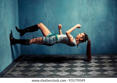 woman in boots and jeans shorts climb up  the wall in grungy room - stock photo