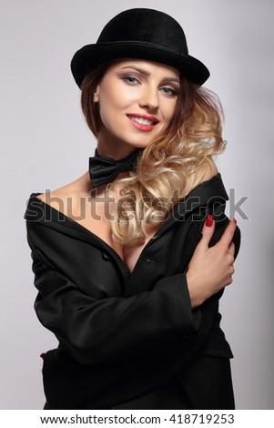 Woman in bowler hat smiling. - stock photo