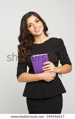 woman in business black dress holding an office notebook. She has gorgeous dark hair and tanned skin and a beautiful smile. She likes her job. - stock photo