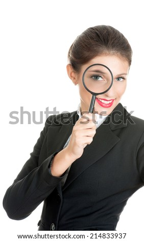 Woman in business dress looking through a magnifying glass. She is searching for something. - stock photo