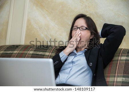 Woman in business suit yawning on sofa with laptop - stock photo