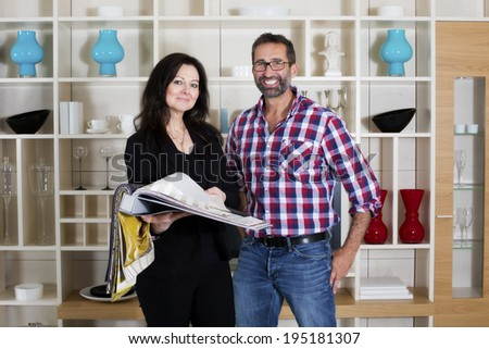 woman in businessuit consults a man standing in a living room - stock photo