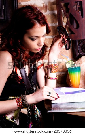 woman in cafe reading magazine - stock photo