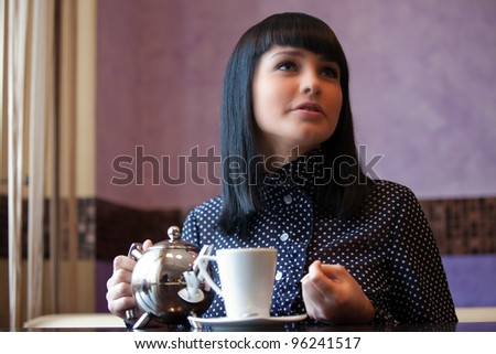 woman in cafe with teapot in hands - stock photo