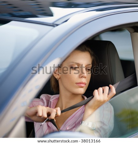 woman in car fastening safety belt - stock photo