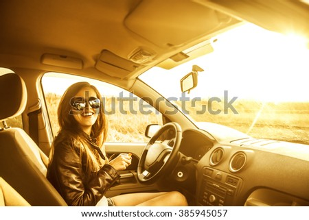 woman in car indoor keeps wheel turning around smiling looking at passengers in near seat. idea taxi driver sit against sunset rays Light shine sky Concept of exam Vehicle - second home the girl - stock photo