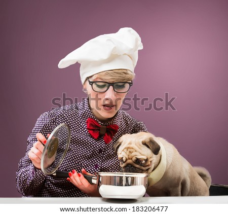 Woman in chef's hat and her dog tasting food, purple background - stock photo