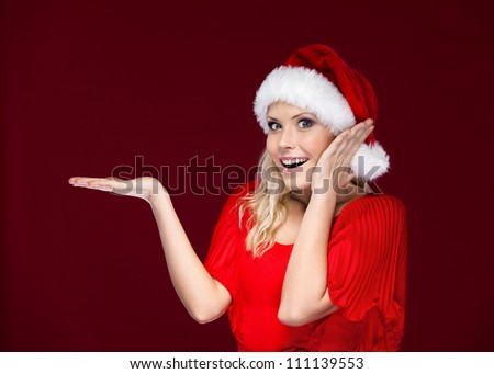 Woman in Christmas cap gestures palm up, isolated on purple - stock photo