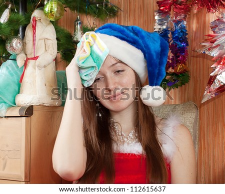 Woman in christmas hat having hangover at home - stock photo