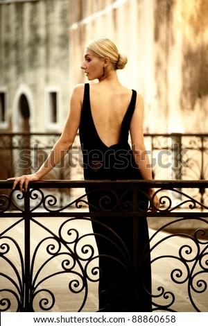Woman in classic dress on a bridge - stock photo
