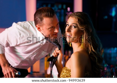 Woman in club dragging the barkeeper over the bar counter - stock photo