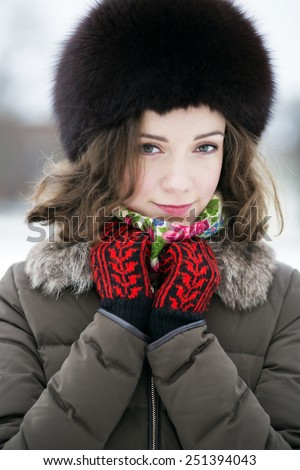 Woman in colored mittens looking shy and calm - stock photo