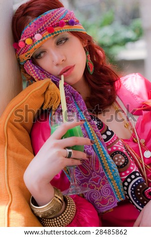 woman in colorful clothes drinking juice - stock photo