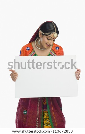 Woman in colorful lehenga choli holding a placard - stock photo