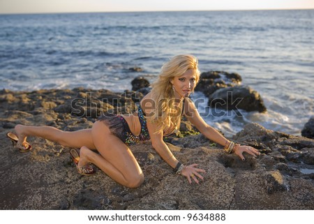 Woman in colorful outfit crawling on rocks at the beach - stock photo