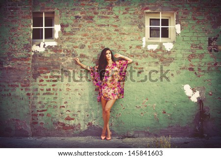 woman in colorful summer dress lean on old brick wall outdoor shot summer day - stock photo