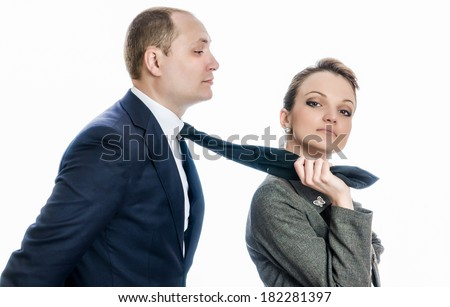 Woman in control of a man, sexy woman holding her man by his tie dominating him  - stock photo