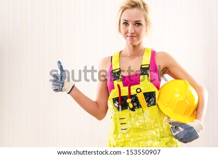 Woman in coverall holding hard hat and showing thumbs up  - stock photo