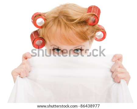 Woman in curlers hides her face on a white background. - stock photo
