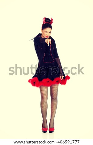 Woman in devil carnival costume pointing on you.  - stock photo