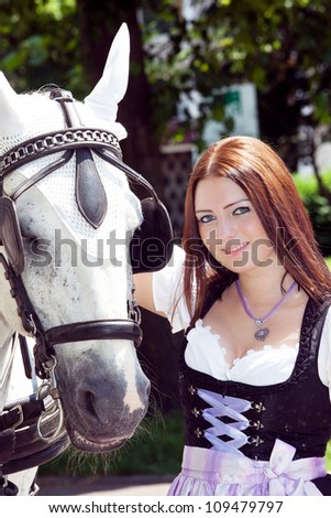 Woman in dirndl with horse - stock photo