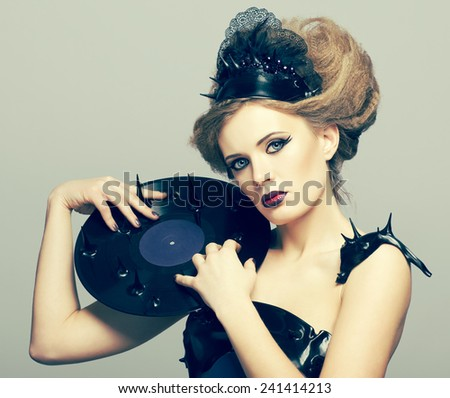 Woman in dress and diadem made of molten vinyl disk with record in hands - stock photo