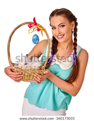 Woman in easter style holding eggs and live rabbit. - stock photo