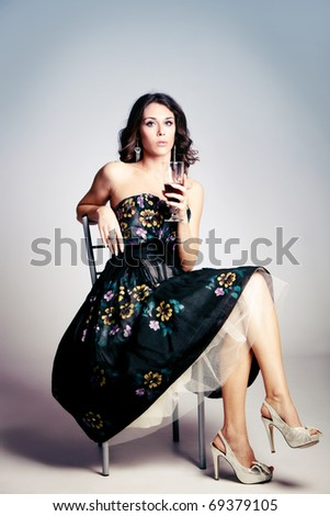 woman in elegant dress sit and hold a glass of red wine, studio shot - stock photo