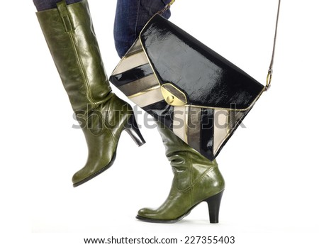 woman in fashion boots and trendy bag steps - stock photo