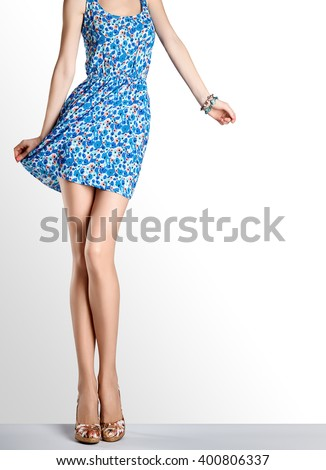 Woman in fashion sundress and high heels. Female sexy long legs, model pose, stylish flower sundress and summer glamour shoes on legs. Unusual creative elegant sexy girl in pose. Fashion female outfit - stock photo