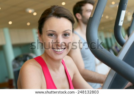 Woman in fitness club using cardio equipment - stock photo