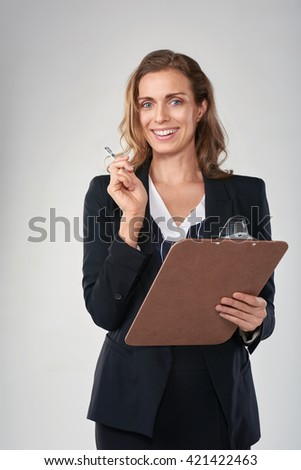 Woman in formal business suit holding a clipboard recording survey results information - stock photo