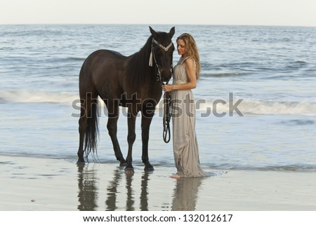 woman in formal dress in ocean with horse, time exposure showing motion of waves - stock photo