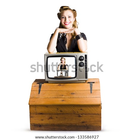 Woman in front of  an unseen TV camera with her picture shown on a television monitor placed on top of a polished pine chest isolated on white background - stock photo