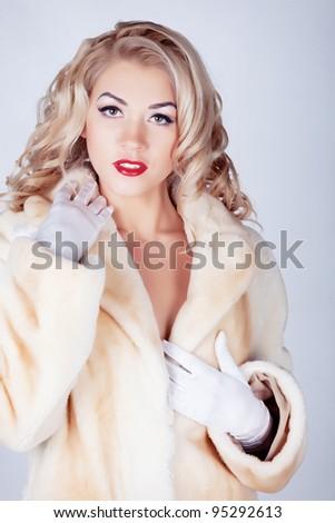 Woman in fur coat in studio - stock photo