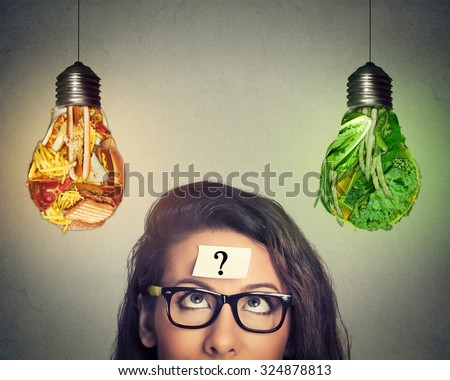Woman in glasses question mark on head thinking looking up at junk food and green vegetables shaped as light bulb isolated on gray background. Diet choice right nutrition healthy lifestyle concept   - stock photo
